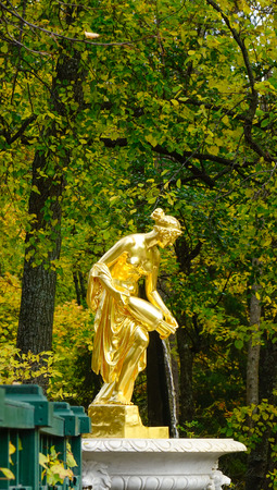 St. Petersburg, Russia - Oct 9, 2016. A Golden God statue at the Peterhof garden at autumn in Saint Petersburg, Russia. Several fountains are designed with the specific purpose of soaking visitors. Editorial