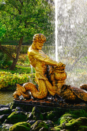 St. Petersburg, Russia - Oct 9, 2016. A fountain with God statue at the Peterhof garden in Saint Petersburg, Russia. The gardens are sometimes referred as the Russian Versailles.