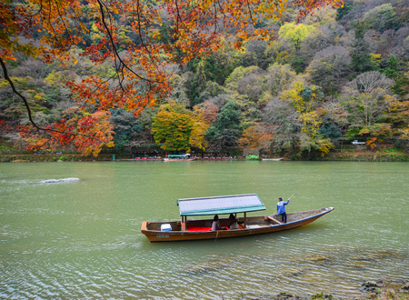 boatman: Kyoto, Japan - Nov 28, 2016. Boatman punting the boat for tourists to enjoy the autumn view with maple trees along the bank of Hozu river in Arashiyama, Kyoto, Japan.
