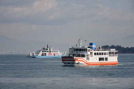 Hiroshima, Japan - Dec 28, 2015. Ferries running on the sea to Miyajima Island in Hiroshima, Japan. Miyajima is famous for the Itsukushima Shrine, a UNESCO World Heritage Site.