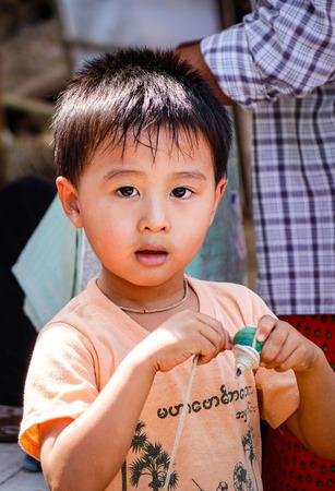 MANDALAY, MYANMAR - FEB 19, 2016. A Burmese boy posing for camera near one of holy temples of Mandalay city in Myanmar (Burma).