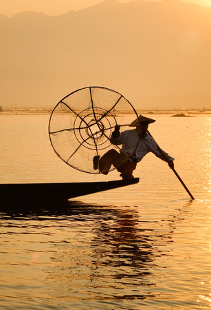 An Intha fisherman using his unique methods of rowing and catching fish on Inle Lake at early morning in Shan State, Myanmar.