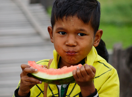 Yangon, Myanmar - Feb 26, 2016. A Burmese child eating watermelon at rural village in Yangon, Myanmar. Yangon is the countrys largest city with a population of nearly 6 million.