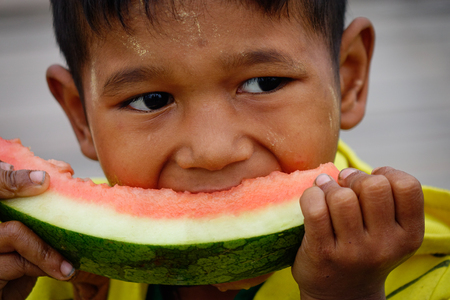 Yangon, Myanmar - Feb 26, 2016. A Burmese boy eating watermelon at rural village in Yangon, Myanmar. Yangon is the countrys largest city with a population of nearly 6 million. Editorial