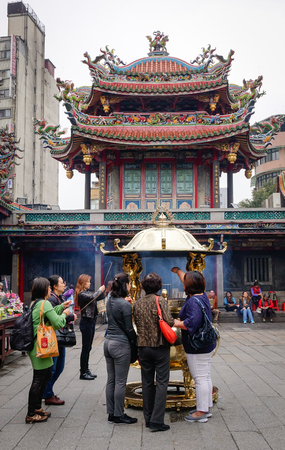 worshipped: TAIPEI, TAIWAN - JAN 5, 2016. Many people including Taiwanese and tourists with believers come to Longshan Temple. The temple is one of the most famous worshipped temples in Taiwan.