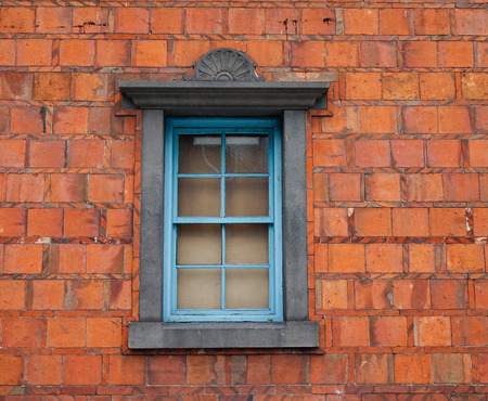 Red brick wall with an old window at the old temple in Asia.