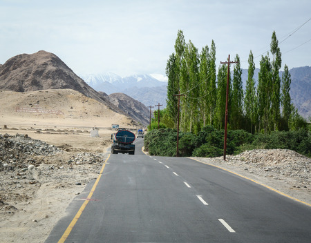 Ladakh, India - Jul 17, 2015. A truck running pass the road on high altitude Ladakh-Leh road in India. Ladakh is one of the most sparsely populated regions in Jammu and Kashmir. Editorial