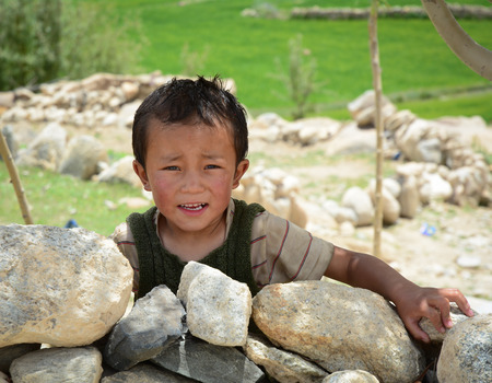 Leh, India - Jul 17, 2015. A Tibetan boy at a village in Nubra Valley, India. 65% of children attend school, but absenteeism of both students and teachers remains high.