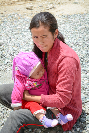 Leh, India - Jul 17, 2015. A Tibetan woman with her son at a village in Nubra Valley, India. 65% of children attend school, but absenteeism of both students and teachers remains high.