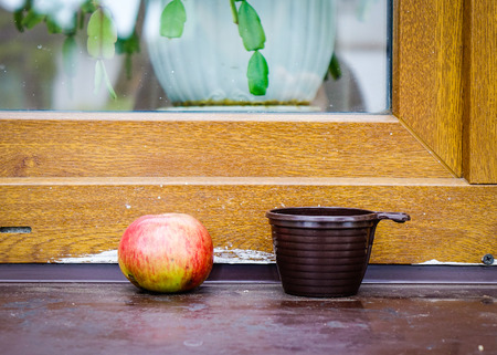 Apple and a cup with wooden window at village in Suzdal, Russia.