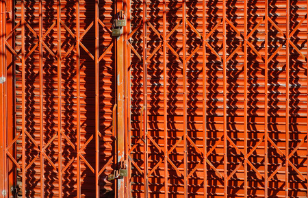 Red steel door at the ancient town under the sun light. Stock Photo