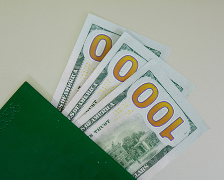 American banknotes (US dollars) with green passport - close up. The United States dollar is the official currency of the United States and its insular territories per the United States Constitution.