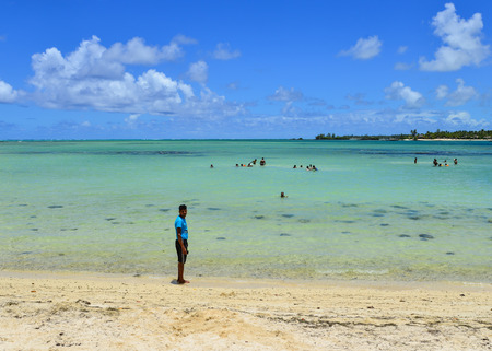 Grand Baie, Mauritius - Jan 7, 2017. A man walking on the beach in Grand Baie, Mauritius. Mauritius is a major tourist destination, ranking 3rd in the region and 56th globally.