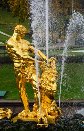 St Petersburg, Russia - Oct 9, 2016. Golden God Statue with foutain at Peterhof in Saint Petersburg, Russia. Peterhof palaces and gardens are sometimes referred as the Russian Versailles.