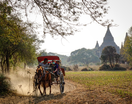 horse cart: Bagan, Myanmar - Feb 18, 2016. Horse cart carrying tourists on dusty road in Bagan, Myanmar. Bagan is an ancient city and one of Asias most important archeological sites.