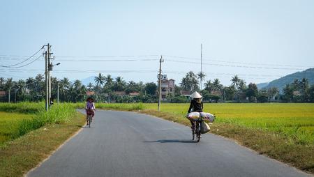 vietnamese ethnicity: Mekong Delta, Vietnam - Mar 23, 2016. People biking on rural road in Mekong Delta, Vietnam. 2.6 million ha in the Mekong Delta are used for agriculture.