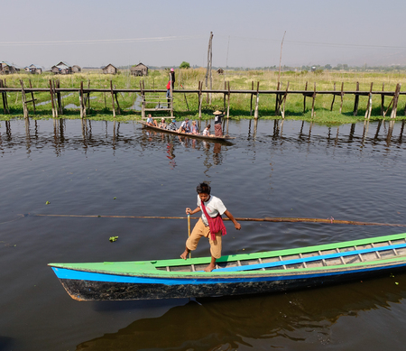 inlay: Inle, Myanmar - Feb 14, 2016. A man rowing wooden tourist boat on Inle lake, Myanmar. Inle Lake is a freshwater lake located in the Nyaungshwe Township of Shan State.