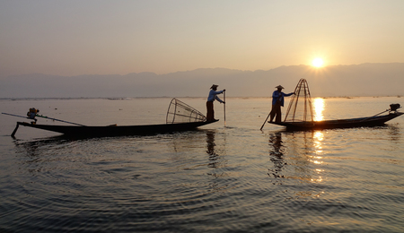 Intha fishermen use their unique methods of rowing and catching fish on Inle Lake at early morning in Shan State, Myanmar.