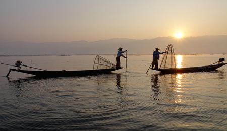 Intha vissers gebruik maken van hun unieke methodes van het roeien en het vangen van vis op Inle Lake op de vroege ochtend in de Shan Staat, Myanmar.