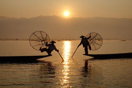 Intha people use the unique methods of rowing and catching fish on Inle Lake in Myanmar. Inle is a beautiful highland lake, 900 meters above sea level. Stock Photo
