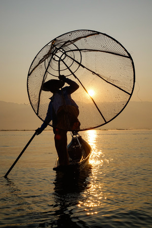 inlay: A Burmese man using the unique methods of rowing and catching fish on Inle Lake at early morning in Shan State, Myanmar.