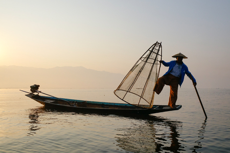 Inle, Myanmar - Feb 14, 2016. A Burmese man using the unique methods of rowing and catching fish on Inle Lake at early morning in Shan State, Myanmar.