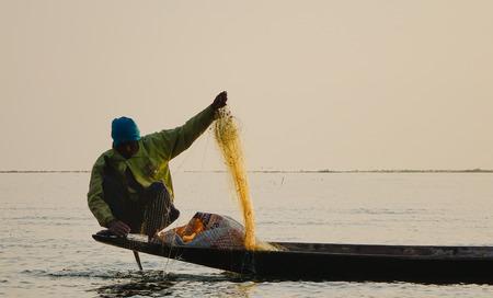 Inle, Myanmar - 14 februari 2016. En burmesisk man som fångar fisk på Inle Lake, Shan State, Myanmar. Inle är en av de högsta sjöarna i en höjd av 2 900 fot (880 m).