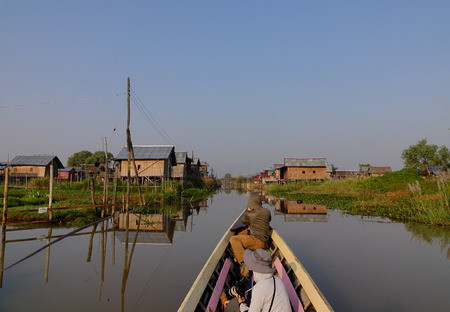 entrapment: Inle, Myanmar - Feb 15, 2016. Tourists visit by wooden boat on Inle lake, Shan state, Myanmar. Inle Lake is a major tourist attraction, and this has led to some development of tourist infrastructure.