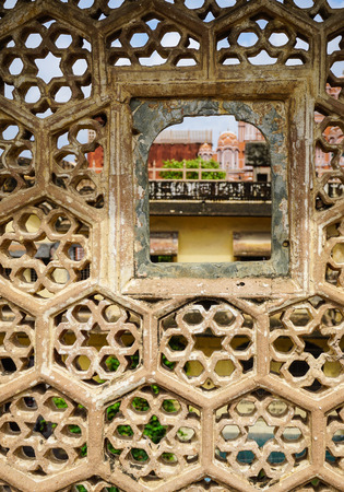 louver: Stone louver with window at the ancient castle in Jaipur, India. Jaipur is a land of natural beauty and great history of travel destinations.