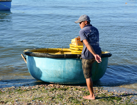 mam: Phan Thiet, Vietnam - Mar 19, 2016. A man with the basket boat in Phan Thiet, Vietnam. The bustling port city of Phan Thiet is traditionally known for its nuoc mam (fish sauce).