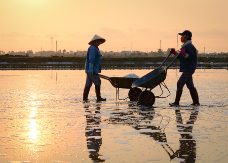 Khanh Hoa, Vietnam - Mar 21, 2016. People working on salt fields at the sunny day in Ninh Hoa, Khanh Hoa, Vietnam. Ninh Hoa is considered one of the largest salt fields nationwide. Editorial