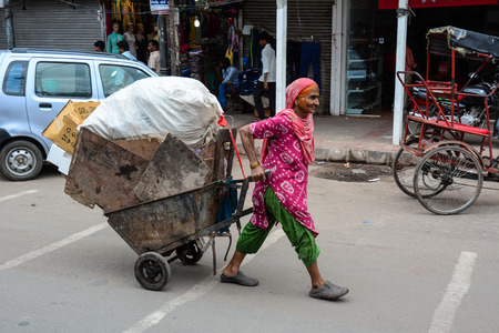 overcrowded: Delhi, India - Jul 26, 2015. A woman carrying goods at the old market in Delhi, India. According to the 2011 census of India, the population of Delhi is 16,753,235. Editorial