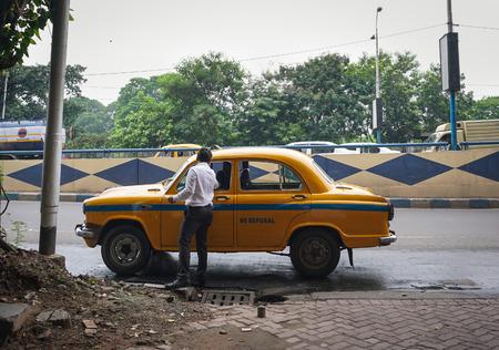 Kolkata, India - el 8 de julio de 2015. Un hombre que toma el taxi en la calle en Kolkata, la India. Kolkata es la ciudad más grande en la India Oriental, así como en la región histórica de Bengala. Editorial