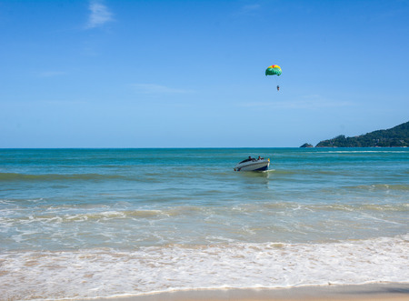 kiting: Phuket, Thailand - Jun 19, 2016. People playing parasailing in Phuket, Thailand. Phuket is a melting pot of indigenous Thais, Chinese, ethnic Malays and even sea gypsies.