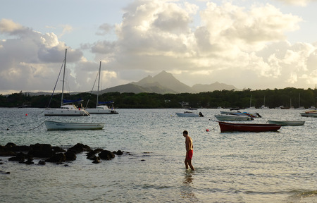 Grand Baie, Mauritius - Jan 11, 2017. A man enjoying on the beach at sunset in Grand Baie, Mauritius. Mauritius was uninhabited until 1598, and had much unique wildlife and plant life.