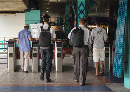 Kuala Lumpur, Malaysia - Jun 6, 2015. People at the entrance of metro station in Kuala Lumpur, Malaysia. Rail transport in Kuala Lumpur encompasses the light metro (LRT) and monorail.