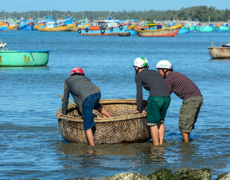 ne: Binh Thuan, Vietnam - Jan 28, 2016. Fishermen using a basket boat at pier in Binh Thuan, Vietnam. Binh Thuan Province is known for its beaches and coastal roads. Editorial