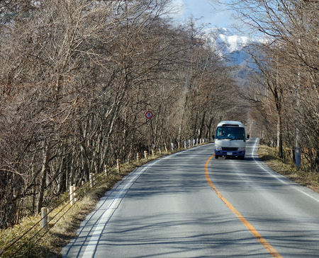 uninhabited: Nikko, Japan - Jan 2, 2016. A bus runs on mountain road in Nikko, Japan. Nikko and Lake Chuzenji, in particular, are well known for their beautiful autumn colors (koyo).