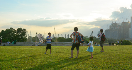 Singapore - Mar 12, 2016. People enjoy at the green park in Singapore. As of mid-2015, the estimated population of Singapore was 5,535,000 people.