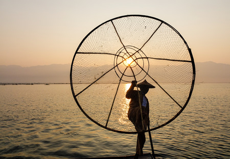 hype: An Intha fisherman catching fish on Inle Lake at sunrise in Shan, Myanmar. The Inle Lake region is one of Myanmar most anticipated destinations and all the hype is justified. Stock Photo