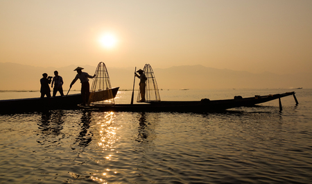 Intha people catching fish on Inle Lake in Shan, Myanmar. Inle is a beautiful highland lake, 900 meters above sea level. Stock Photo