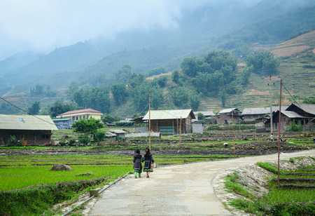 frontier: Sapa, Vietnam - May 30, 2016. Hmong girls walking on rural road in Sapa, Vietnam. Sa Pa is a frontier township in Lao Cai Province in north-west Vietnam. Editorial