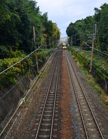 A train running on the rail track near Arashiyama Station in Kyoto, Japan.