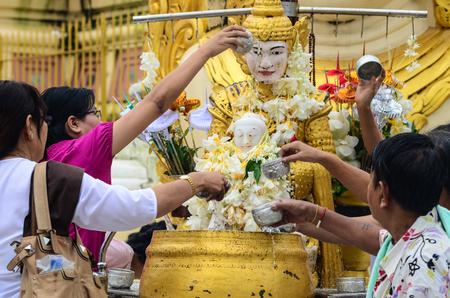 Yangon, Myanmar - Oct 1, 2011. People bathing Buddha at Shwedagon Pagoda in Yangon, Myanmar. Shwedagon is the most sacred Buddhist pagoda in Myanmar. Stock Photo - 73699340