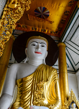 reconstruct: Yangon, Myanmar - Oct 1, 2011. Golden Buddha statue at main hall in Shwedagon Paya in Yangon, Myanmar. Shwedagon Pagoda is the most sacred Buddhist pagoda in Myanmar.