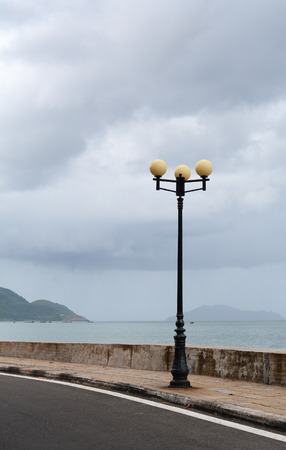 Lamp post on rural road at rainy day with seascape background
