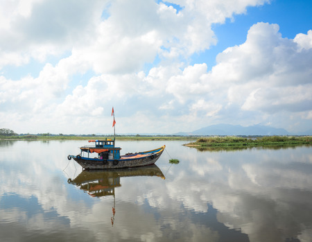 Fishing boat docking on the Hoai river at sunny day in Hoi An ancient town, Vietnam.