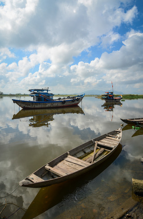 Wooden boats docking on the Hoai river at sunny day in Hoi An ancient town, Vietnam. Hoi an is recognized as a World Heritage Site by UNESCO. Editorial