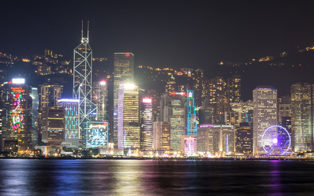 characterised: Hong Kong - Dec 27, 2014. View of business district in Hong Kong at night. Hong Kong has a major capitalist service economy characterised by low taxation and free trade.