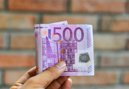 euromoney: A hand holding the Five hundreds (500) Euro banknote with brick wall background